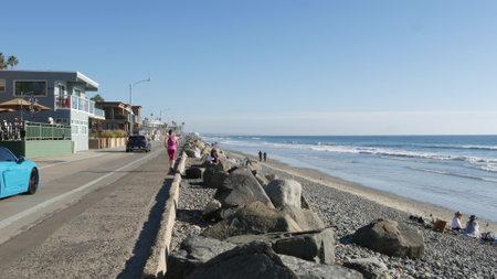 Oceanside, California USA - 16 Feb 2020: People walking strolling on waterfront sea promenade, beachfront boardwalk near pier. Vacations ocean beach resort near Los Angeles. Blue porsche cabriolet car