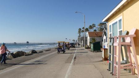 Oceanside, California USA - 16 Feb 2020: People walking strolling on waterfront sea promenade, beachfront boardwalk near pier. Vacations ocean beach resort near Los Angeles. Double bench surrey bike. Editorial