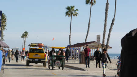 Oceanside, California USA -16 Feb 2020: People walking strolling, waterfront sea promenade, beachfront boardwalk near pier. Vacations ocean beach resort near Los Angeles. Lifeguard car, surrey bike.