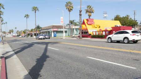 Oceanside, California USA - 20 Feb 2020: Wienerschnitzel hot dog fast food on pacific coast highway 1, historic route 101. Palm trees on street, road along ocean. Road trip vacations in united states.