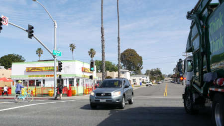 Oceanside, California USA -20 Feb 2020: Wienerschnitzel hot dog fast food, pacific coast highway 1, historic route 101. Palm trees on street, road along ocean. Green garbage truck on road intersection