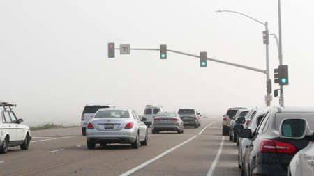 Encinitas, California USA -20 Feb 2020: Traffic light semaphore on highway 101 road by misty beach. Fog on sea shore, pacific ocean coast. Freeway with cars along shoreline, coastline near Los Angeles