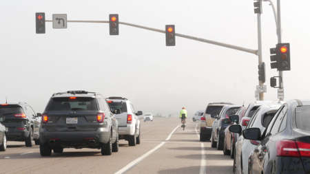 Encinitas, California USA -20 Feb 2020: Traffic light semaphore on highway 101 road by misty beach. Fog on sea shore, pacific ocean coast. Freeway with cars along shoreline coastline. Biker on bicycle
