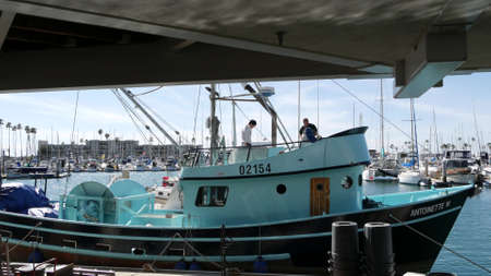 Oceanside, California USA - 26 Feb 2020: Harbor village with fisherman boats and yachts, pacific ocean coast marina, sea shore. Blue nautical vessel for fishing in port, fishery industry. Men working. Standard-Bild - 161603805