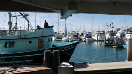 Oceanside, California USA - 26 Feb 2020: Harbor village with fisherman boats and yachts, pacific ocean coast marina, sea shore. Blue nautical vessel for fishing in port, fishery industry. Men working.