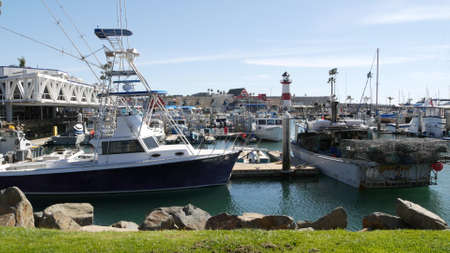 Oceanside, California USA - 26 Feb 2020: Harbor village with fisherman boats and yachts, pacific ocean coast marina, sea shore. Nautical vessel for fishing in port, fishery industry. Lighthouse beacon Standard-Bild - 161603797