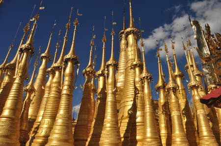Exterior of exotic temple with stupas and payas, From below shot of golden bright stupas of temple on lake Inle under blue sky, Myanmar. Sacred place. Standard-Bild