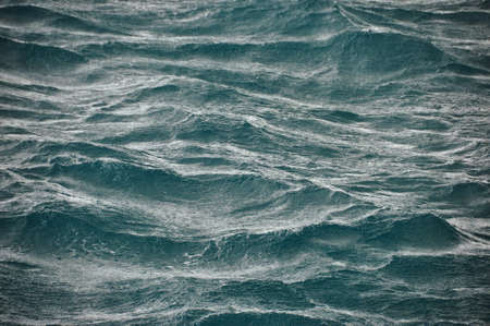 Background of abstract flowing waves of ocean in stormy weather. Rough majestic waves of ocean