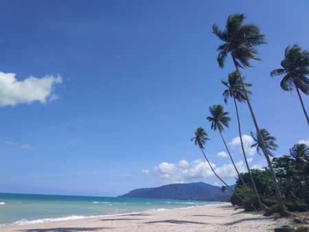 White sandy coast and calm blue sea. idyllic tropical paradise exotic island landscape with green trees and quiet rippling ocean on background of mountains and sky. Quiet surf, low view above water