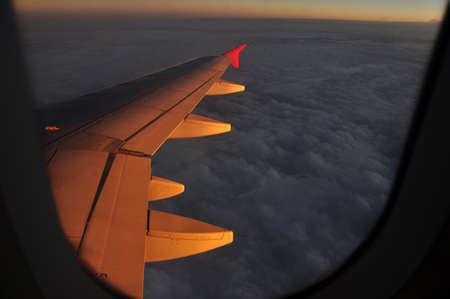 Golden light clouds from plane, View from plane in flight of majestic clouds in golden sunset light illuminating air.