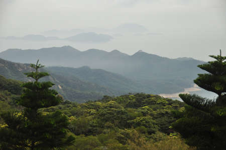 View of silhouette of mountains with lush green tropical woods in mist and fog. Misty landscape of green mountains