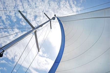 From below shot of white waving sail on tall mast under blue sky in clouds. White sail on mast under blue sky Standard-Bild