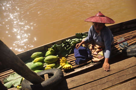 INLE, MYANMAR - NOVEMBER 29, 2015: Ethnic woman on boat with green vegetables, From above of ethnic senior woman on boat near local market with green fruit.