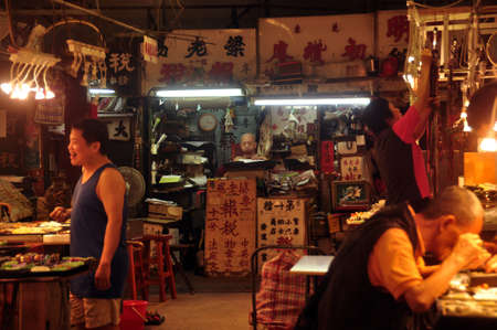 HONG KONG - 21th FEBRUARY, 2015: View of Glowing dark oriental jade market with hieroglyphs on signboards and people in light of lamps. Chinese sellers of jewelry souvenirs.