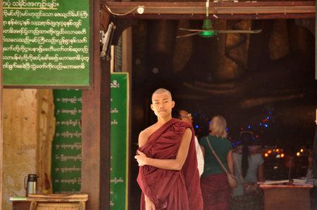 BAGAN, MYANMAR - NOV 13, 2015: Ethnic monk portrait. Young Asian man in robe of monk standing in front of temple entrance. Mingalazedi pagoda. Sulamani Shwezigon Ananda Htilominlo Editorial
