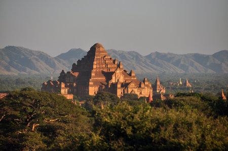 BAGAN, MYANMAR - NOVEMBER 18, 2015: Ancient oriental temple in green terrain, View of beautiful stone Dhammayangyi in green spacious terrain, mountains on background. Mingalazedi Sulamani Shwezigon