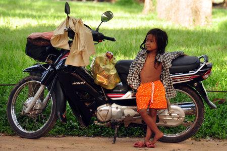 ANGKOR, CAMBODIA - AUG 28, 2013: Little poor ethnic girl standing near motorcycle, Little ethnic girl leaning on motorcycle standing on street.