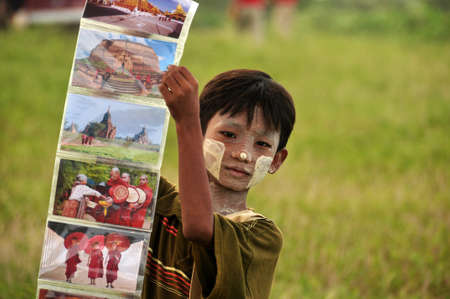 BAGAN, MYANMAR - NOVEMBER 18, 2015: Little ethnic boy showing colorful photos, Cute Asian boy with face paint in tanaka showing collage of colorful photos of oriental culture. Traditional look