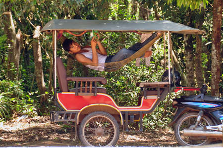 ANGKOR, CAMBODIA - AUG 28, 2013: Side view of man chilling in hammock of tourist carriage outdoors in tropical nature of Angkor Wat. Driver of tourist carriage taking rest
