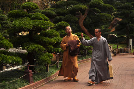 HONG KONG - 22th FEBRUARY, 2015: Monks walking in green oriental garden, View of ethnic monks in robes walking on pathway in Nan Lian garden Editorial