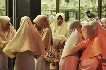 NAKHON SI THAMMARAT, THAILAND - 14 JULY 2016. Group of Muslim women with heads covered standing indoors spending time together. Group of religious women in public Editorial