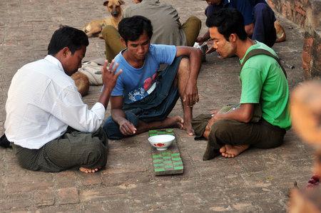 BAGAN, MYANMAR - NOVEMBER 18, 2015: Poor men playing game on street, Side view of group of poor barefoot men sitting on pavement playing oriental game. Portrait Mingalazedi Sulamani Shwezigon Ananda