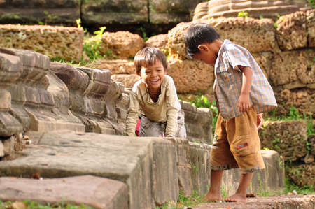 ANGKOR, CAMBODIA - AUG 28, 2013: Cheerful ethnic kids on stone fence, Little Asian boys spending time together on stone fence of ancient temple of Angkor Wat