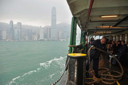 HONG KONG - 21th FEBRUARY, 2015: Sailing Star ferry in blue water of sea with Hong Kong cityscape in mist on background. View of ferry sailing in water with cityscape