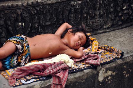 ANGKOR, CAMBODIA - AUG 28, 2013: Sleeping ethnic boy on step of temple, Little ethnic boy sleeping on ornamental rug on stone step of ancient Angkor Wat temple. Mowgli