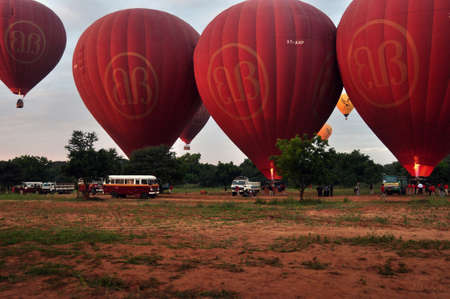 BAGAN, MYANMAR - NOVEMBER 19, 2015: Bright red air balloons on field, View of plenty of red air balloons on ground of spacious terrain. Fly over Mingalazedi Sulamani Shwezigon Ananda Htilominlo