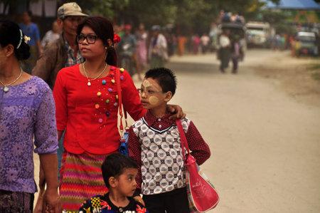 BAGAN, MYANMAR - NOVEMBER 18, 2015 Adult ethnic woman with children in big family walking on street, Myanmar. Ethnic family walking on road Editorial