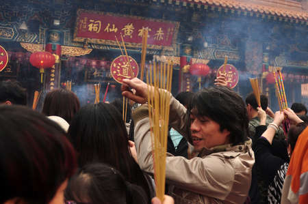 HONG KONG - 22th FEBRUARY, 2015: Crowd of people with aromatic sticks near temple, View of crowded square of people carrying burning sticks in front of Wong Tai Sin temple. Celebrating New Year.