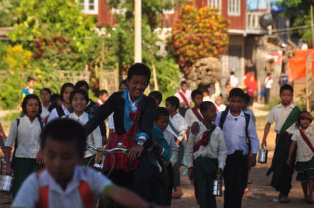 INLE, MYANMAR - NOVEMBER 29, 2015: Children after school walking on street, Group of ethnic kids after school walking on street of village Editorial