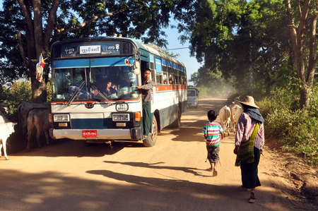 BAGAN, MYANMAR - NOVEMBER 18, 2015: Bus on rural road in village, View of people and cattle on remote rural road with bus under green trees. Mingalazedi Sulamani Shwezigon Ananda Htilominlo
