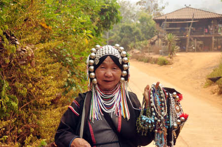 CHIANG MAI, THAILAND - MARCH 1, 2013: Mature ethnic woman with traditional attire in authentic gown and headwear holding heap of traditional adornments in village. Noth tribes Akha, Lisu, Karen, Lahu
