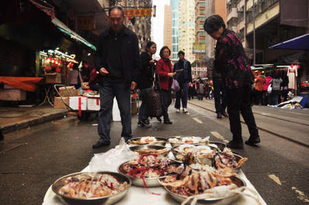 HONG KONG - 22th FEBRUARY, 2015: Local street market with people around, Marine delicatessen on stall for sale on street with people walking around. Street food asia.