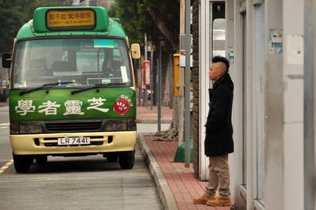 HONG KONG - 21th FEBRUARY, 2015: Man standing on bust stop with colorful bus on roadside near in city of Hong Kong. Modern city dweller on bus stop.
