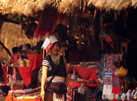 CHIANG MAI, THAILAND - MARCH 1, 2013: Young woman at stall in oriental village wearing traditional gown and standing at stall selling colorful authentic souvenirs. Noth tribes Akha, Lisu, Karen, Lahu
