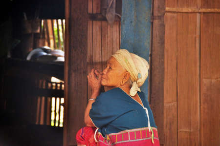 CHIANG MAI, THAILAND - MARCH 1, 2013: Side view of elderly woman of Lisu people sitting on porch of house looking away in rest, Thailand. Senior woman of ethnic Asian tribe
