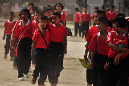 NAKHONSITHAMMARAT, THAILAND - JUNE 7, 2014: Group of pupils of oriental province, Group of many children walking on street of oriental province after school Editorial