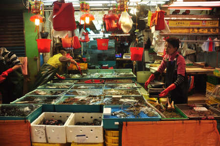 HONG KONG - 22th FEBRUARY, 2015: View of workers sorting fresh catch of seafood in different containers at stall outdoors. People sorting seafood at stall