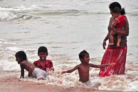 HIKKADUWA, SRI LANKA - 18 DECEMBER 2011 View of adult ethnic woman with group of kids splashing in ocean water waves. Woman with children playing in ocean water Editorial