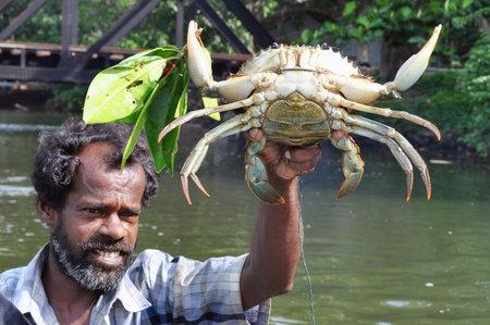 HIKKADUWA, SRI LANKA - 18 DECEMBER 2011 Adult bearded ethnic fisherman with huge caught crab outdoors looking away. Bearded man holding caught crab