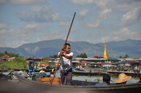 INLE LAKE, MYANMAR - 28 NOVEMBER 2016 View of ethnic man sailing boat pushing with long Editorial