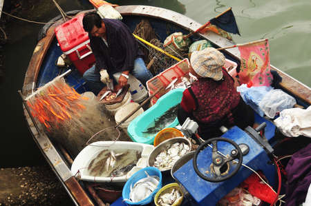 TAI O, HONG KONG - 25th FEBRUARY, 2015: People in fishing boat in village. From above of ethnic fishermen sitting in fishing boat with plenty of containers with fish. Editorial