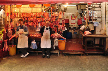 HONG KONG - 22th FEBRUARY, 2015: Ethnic butcher in shop, Men in aprons standing near small shop with meat on background in butchery.