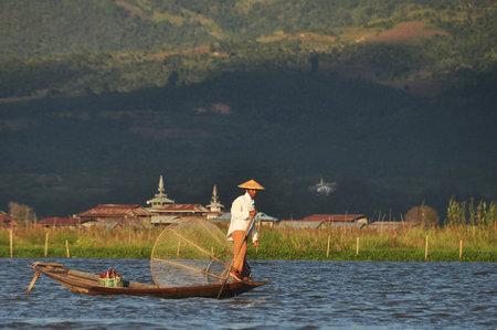 INLE, MYANMAR - NOVEMBER 29, 2015: Fisherman sailing on lake in mountains, View of traditional oriental fisherman on flatboat sailing on Inle lake in sunlight Editorial