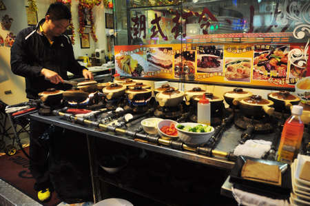 HONG KONG - 23th FEBRUARY, 2015 Asian man cooking street food for sale at stand with pots and cookware, Hong Kong. Ethnic man at stall making street food