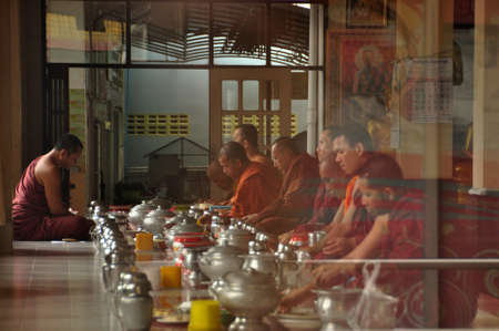 NAKHONSITHAMMARAT, THAILAND - JUNE 7, 2014: Group of monks at table durind. View of men in red robes of monks sitting at table with utensils having meal. Editorial