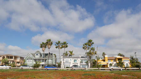 Typical suburban, tropical Carlsbad California USA. Different colorful houses row. Generic american homes, buildings facade, architecture exterior. Residential district real estate. Sky and palm trees